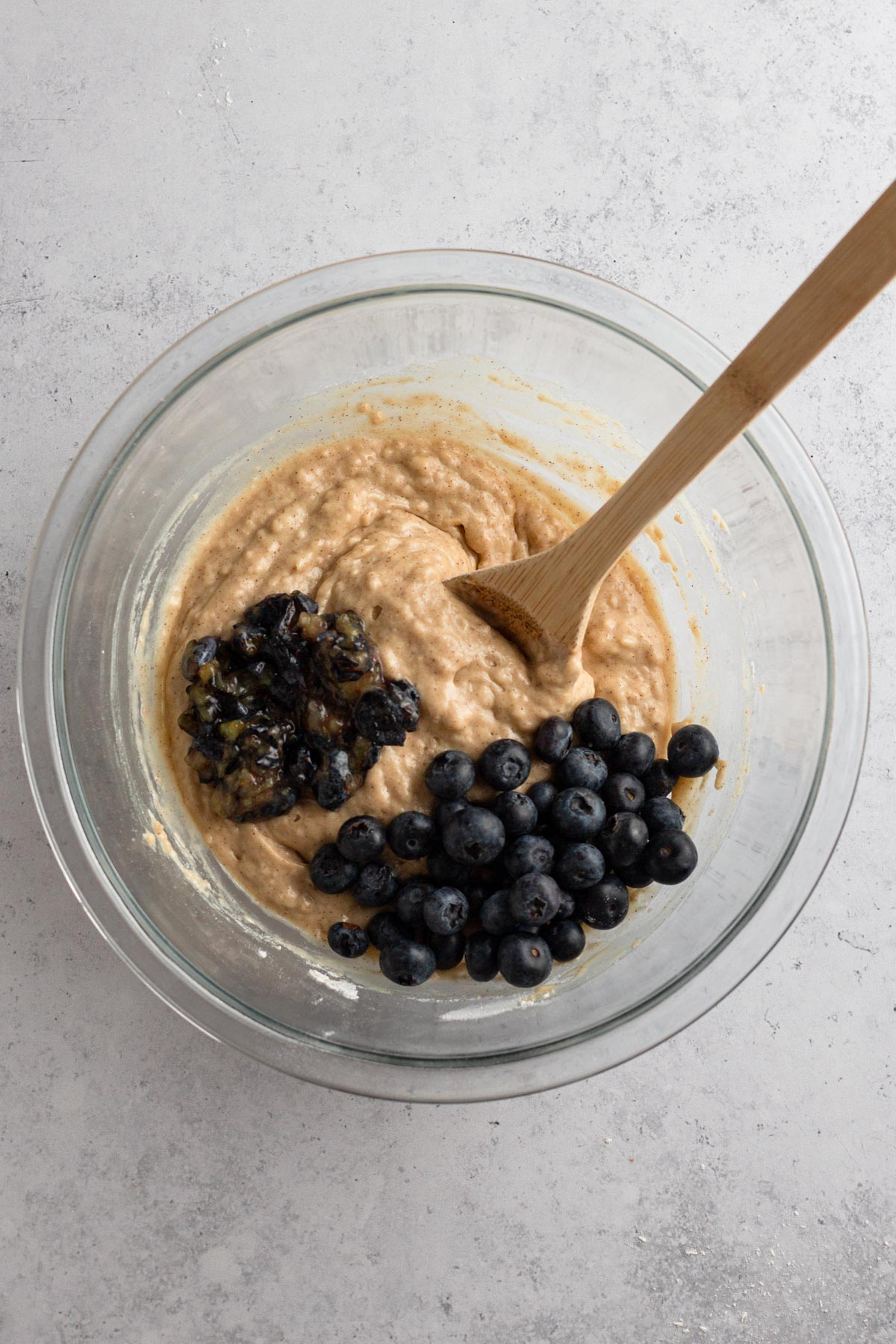 overhead view of muffin batter with blueberries in a glass bowl
