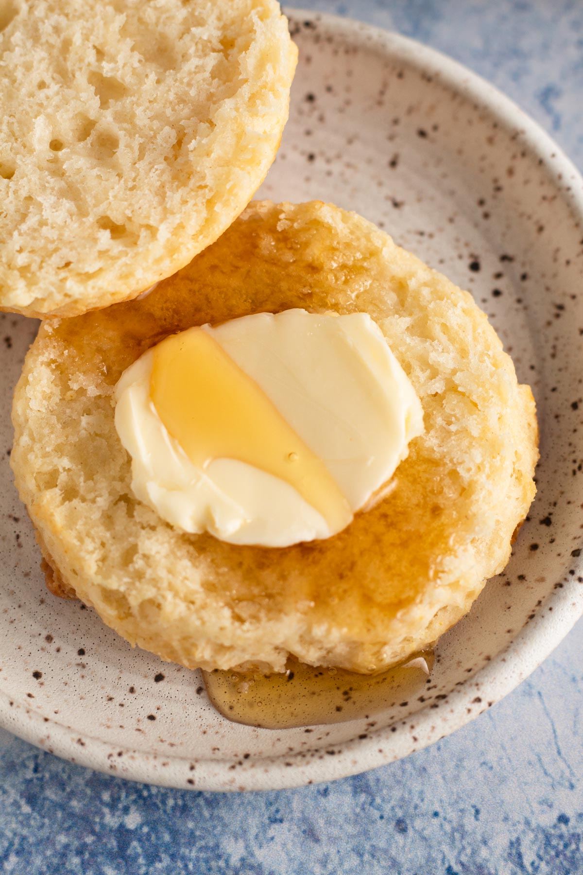 overhead view of a sliced biscuit on a white speckled plate with butter and honey
