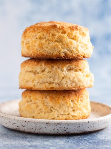 side view of biscuits stacked on a white speckled plate with a blue background