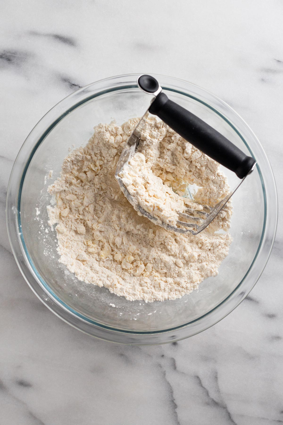 overhead view of dry ingredients in a glass bowl with butter cut in