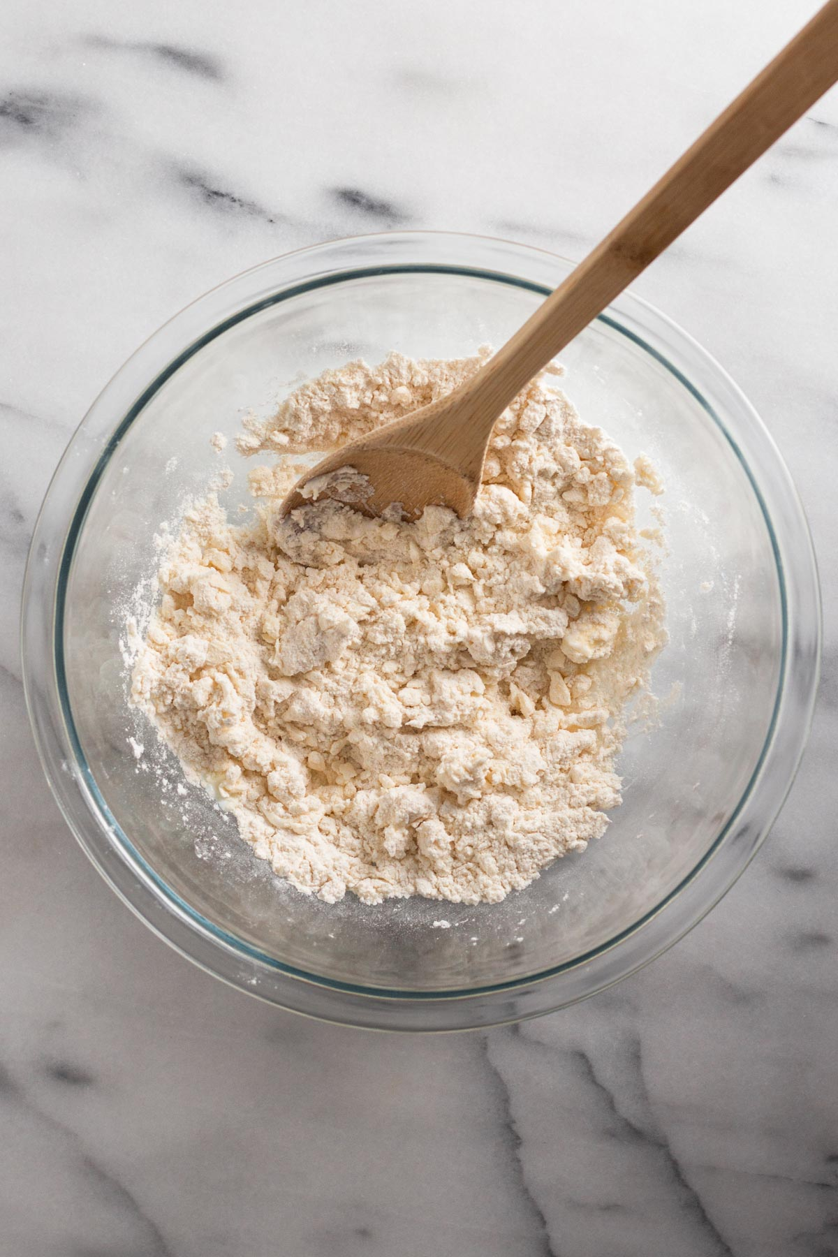 overhead view of crumbly dough in a glass bowl