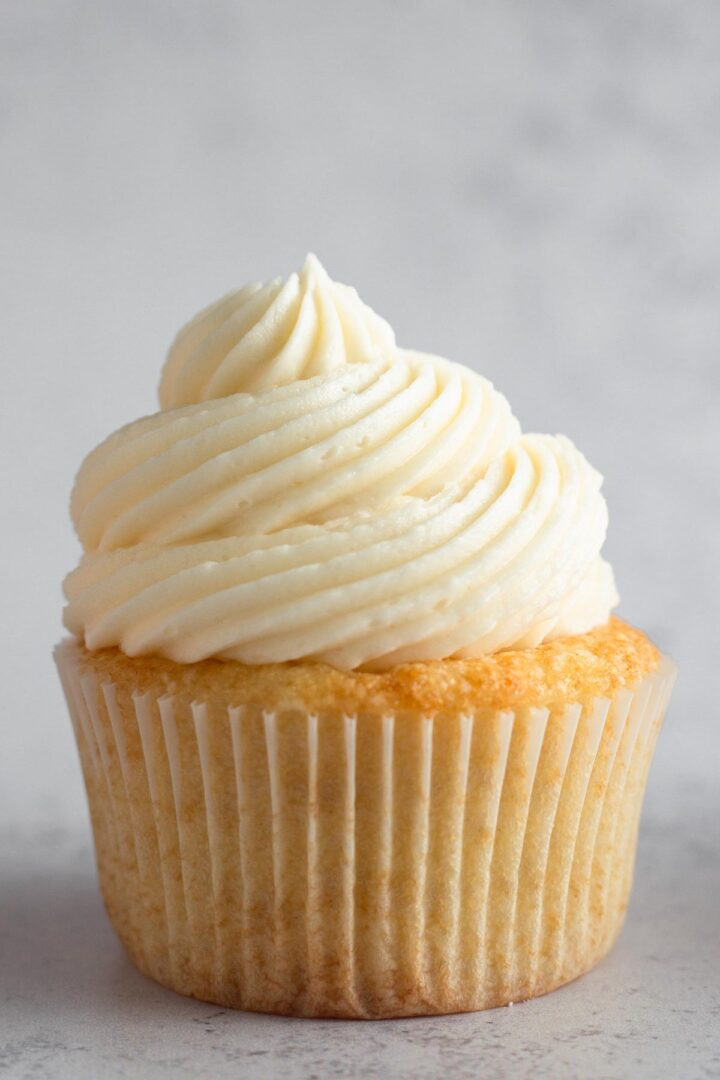 a swirl of vanilla frosting on top of a vanilla cupcake