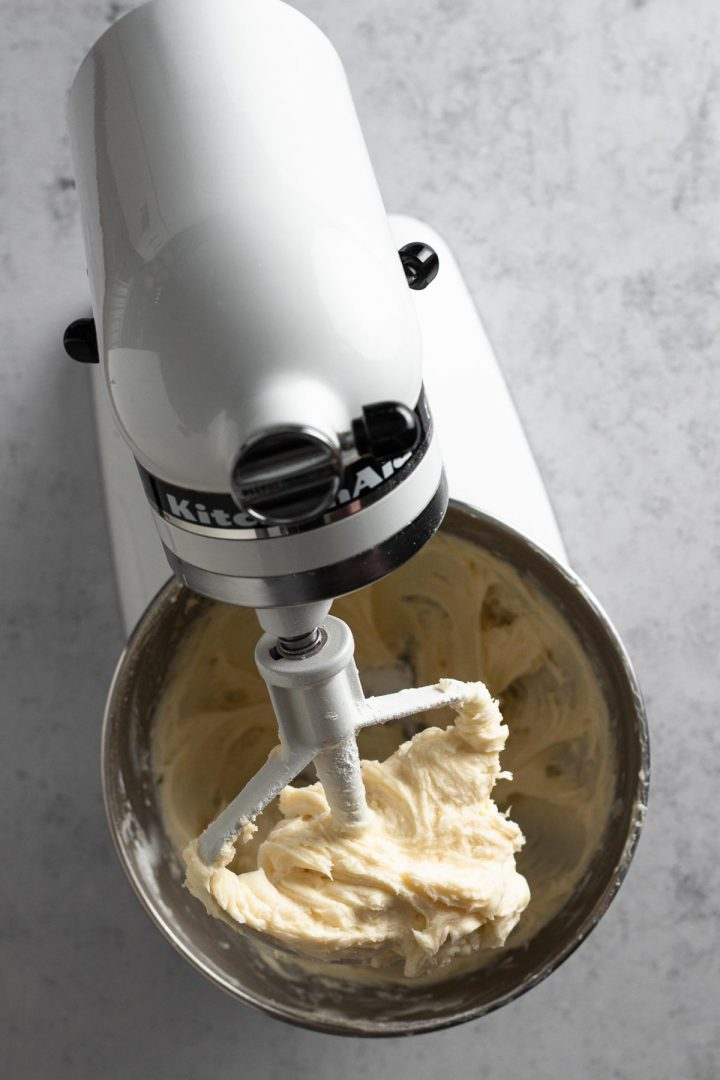 overhead view of butter beaten with some confectioners sugar in a white stand mixer