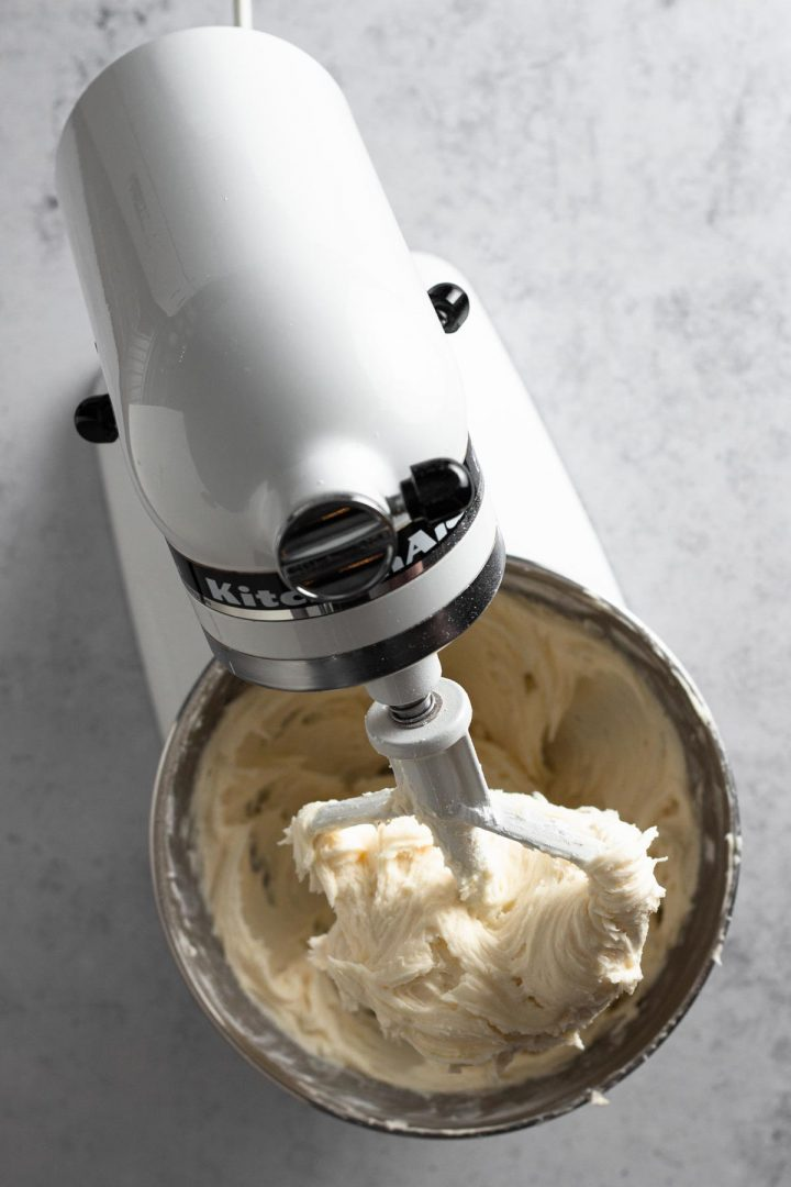overhead view of butter beaten with confectioners sugar in a white stand mixer