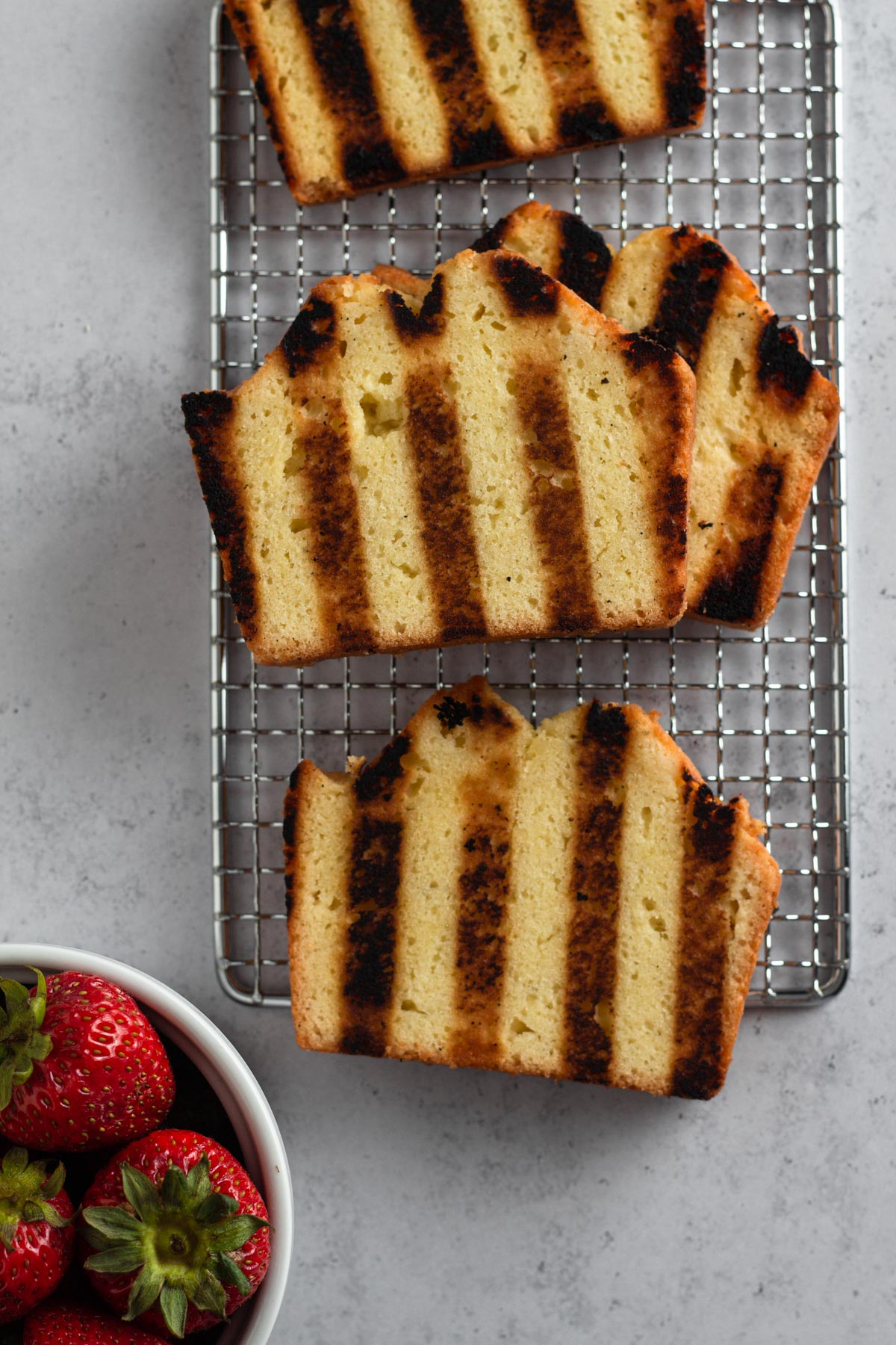 overhead view of grilled pound cake on a cooling rack with a bowl of strawberries