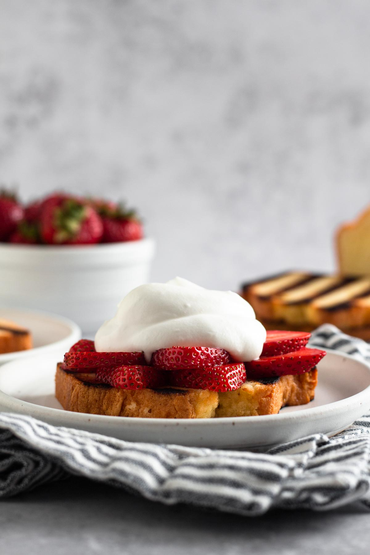 side view of a slice of pound cake topped with sliced strawberries and whipped cream