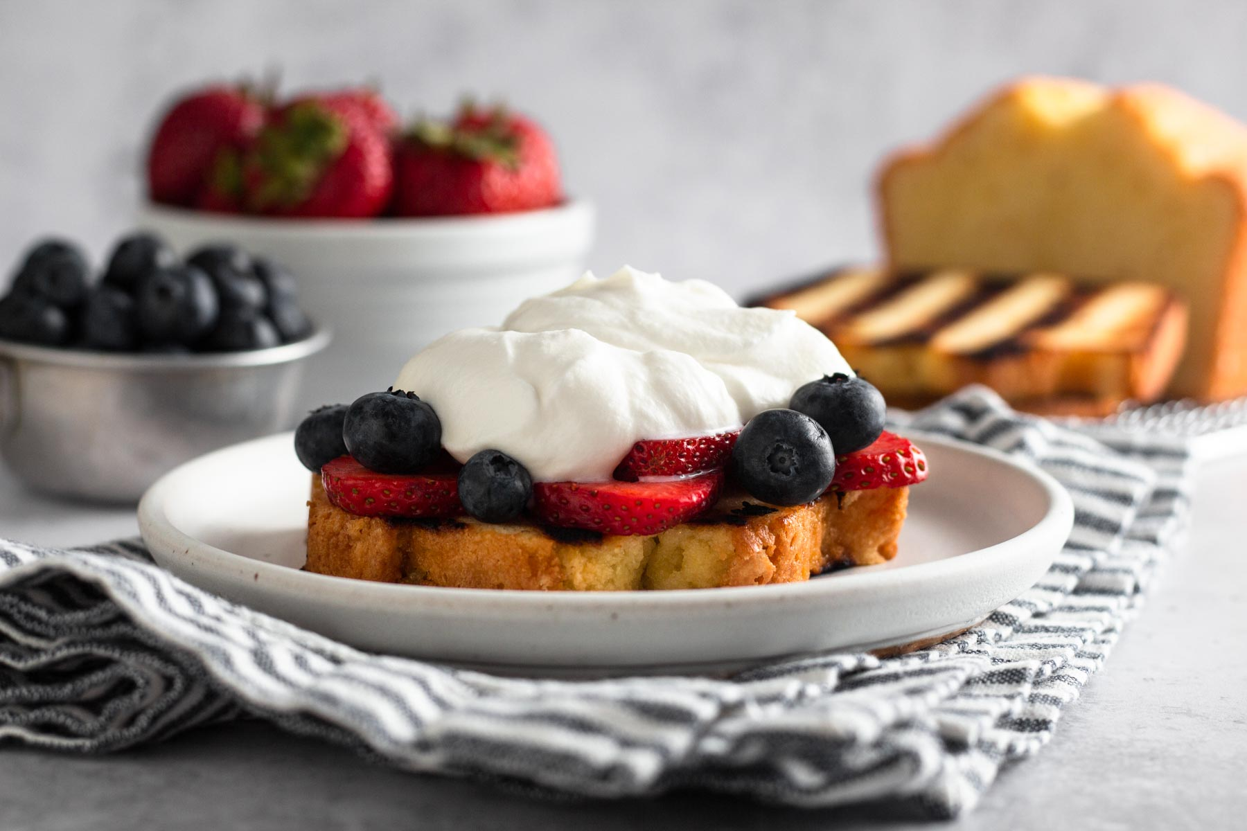 side view of a slice of pound cake topped with sliced strawberries, blueberries, and whipped cream