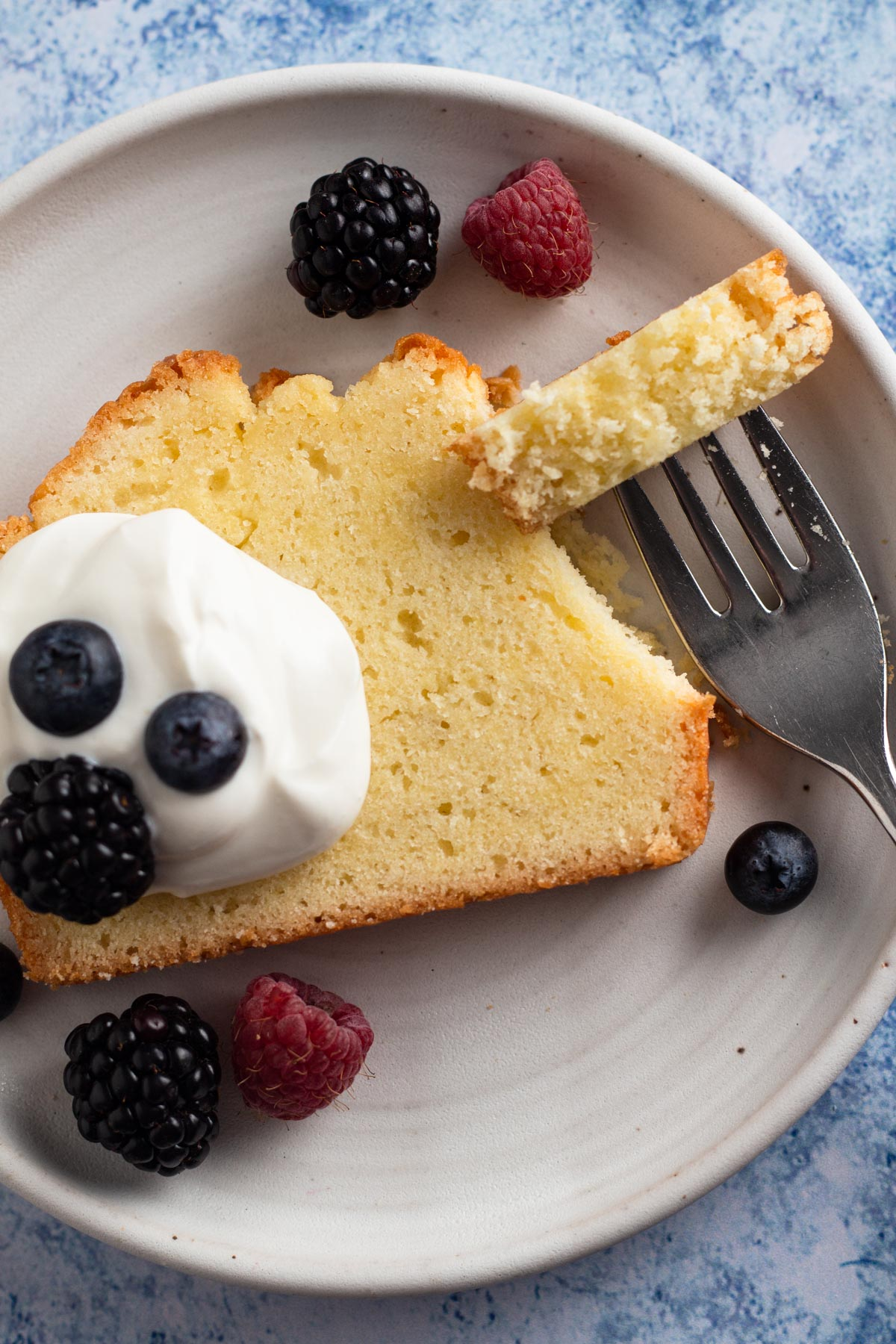 overhead view of a slice of pound cake on a white plate with whipped cream, fresh berries, and a fork