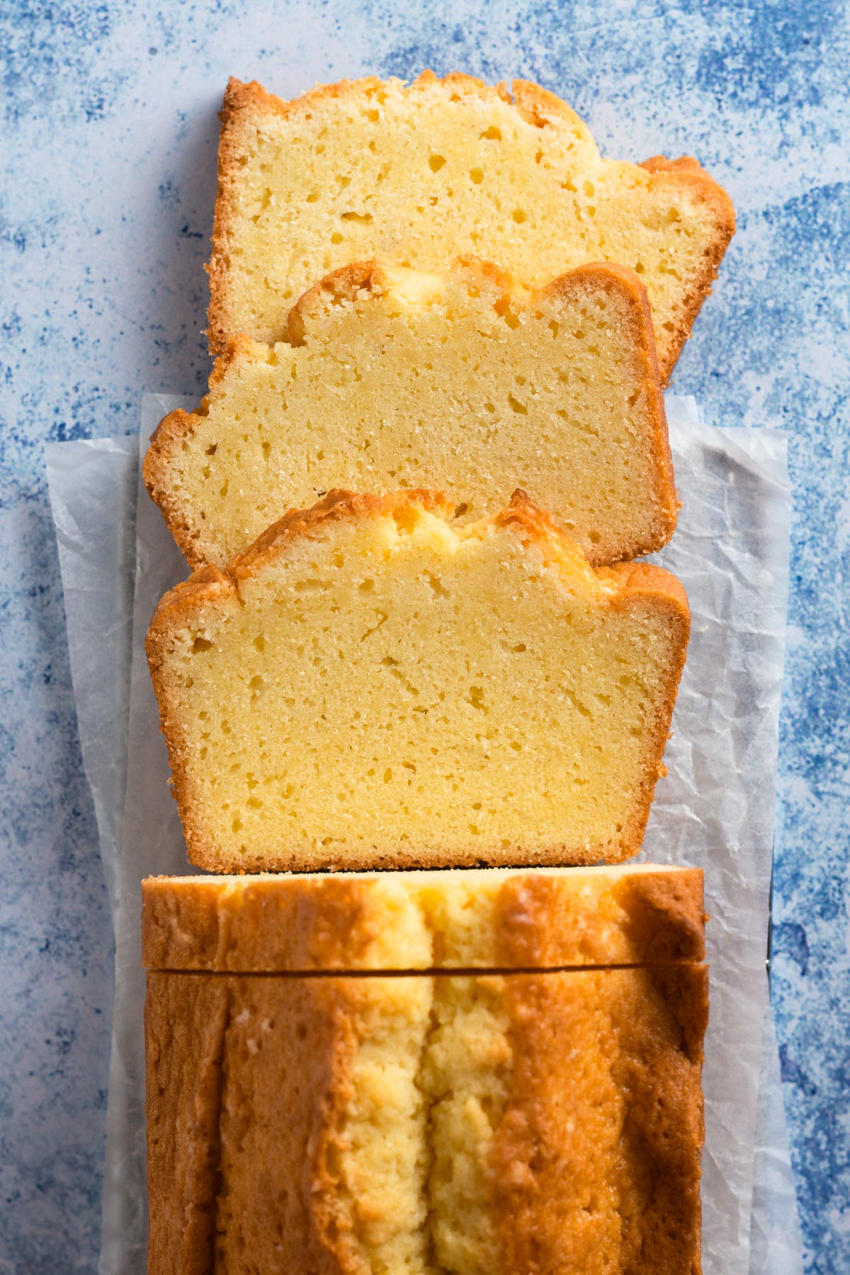 overhead view of a sliced pound cake loaf on a blue surface