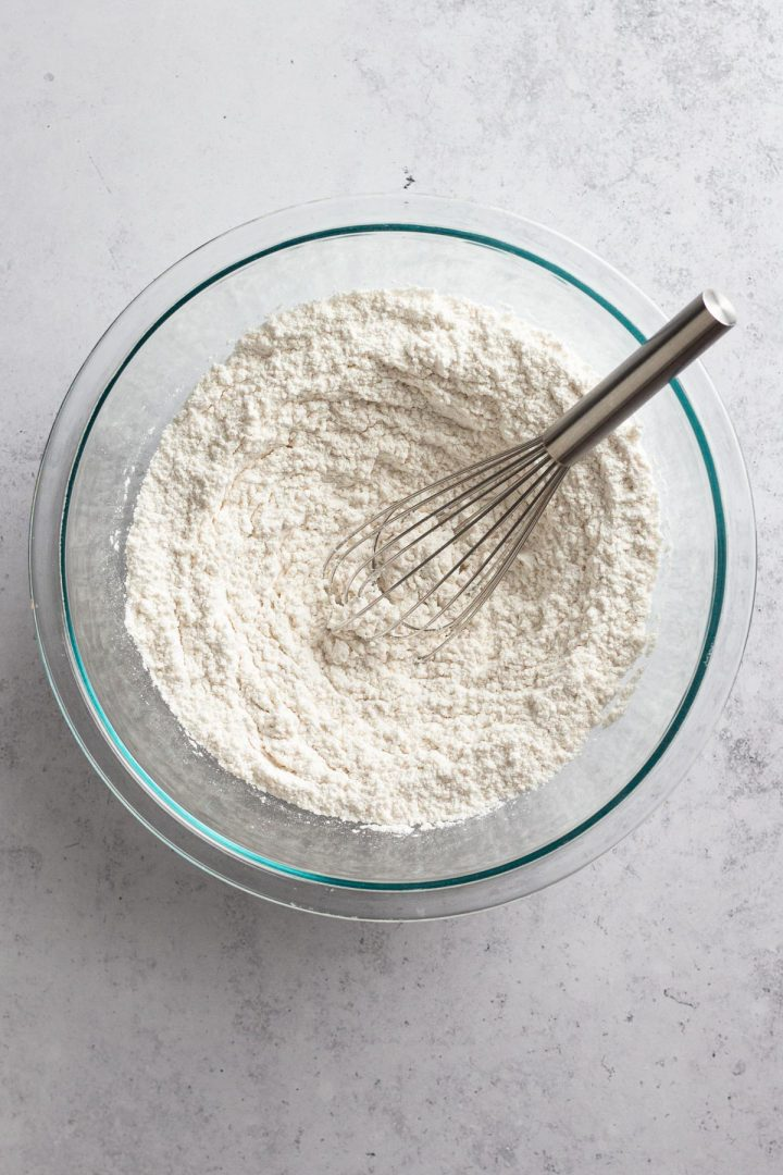 overhead view of dry ingredients in a glass mixing bowl with a metal whisk