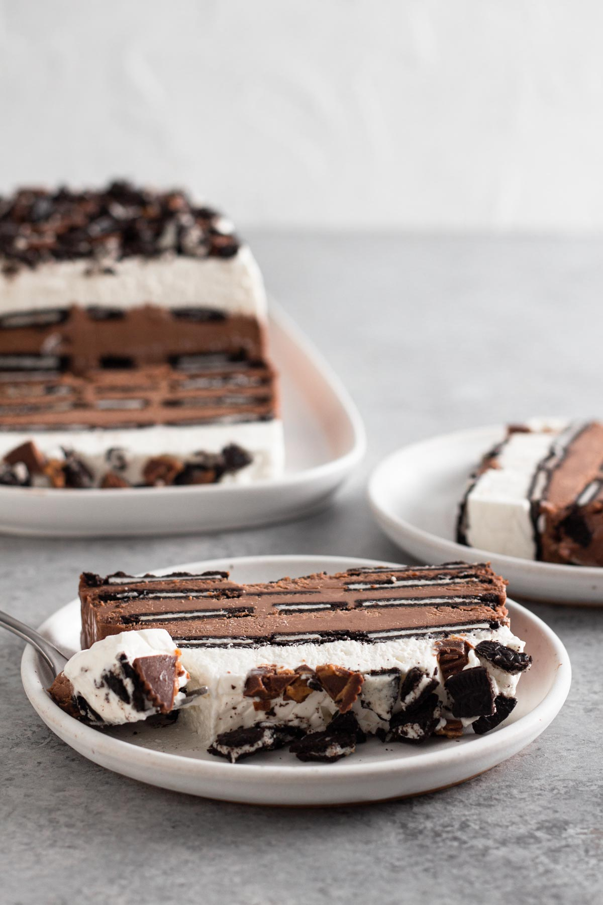side view of slices of icebox cake on white plates on a gray surface