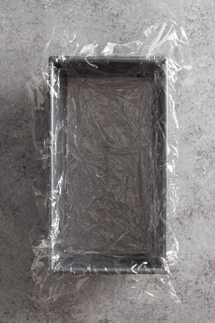 overhead view of loaf pan lined with plastic wrap