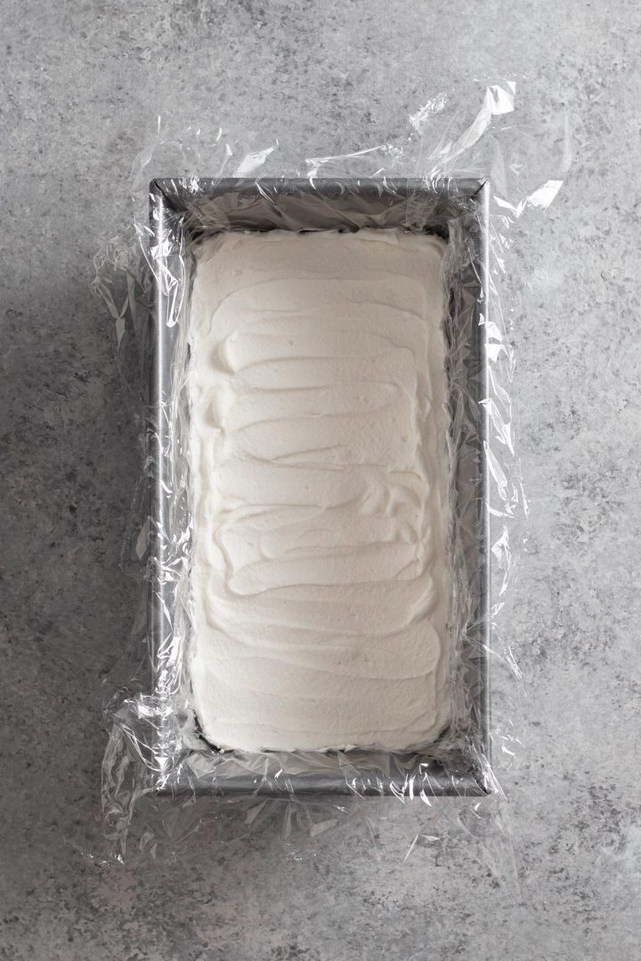 overhead view of loaf pan with whipped cream spread into an even layer in the bottom of the pan