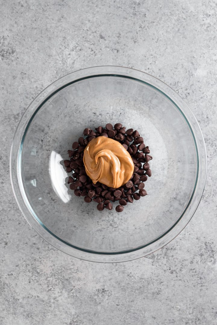 overhead view of chocolate chips and peanut butter in a glass bowl