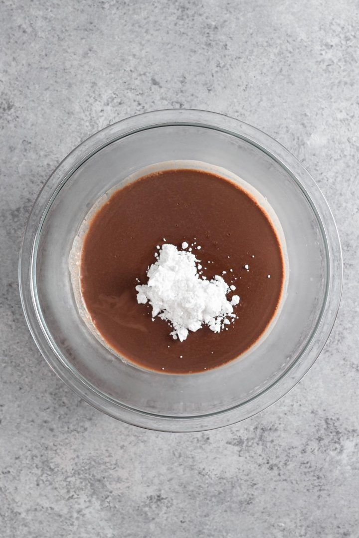 overhead view of chilled chocolate mixture in a glass bowl with confectioners' sugar
