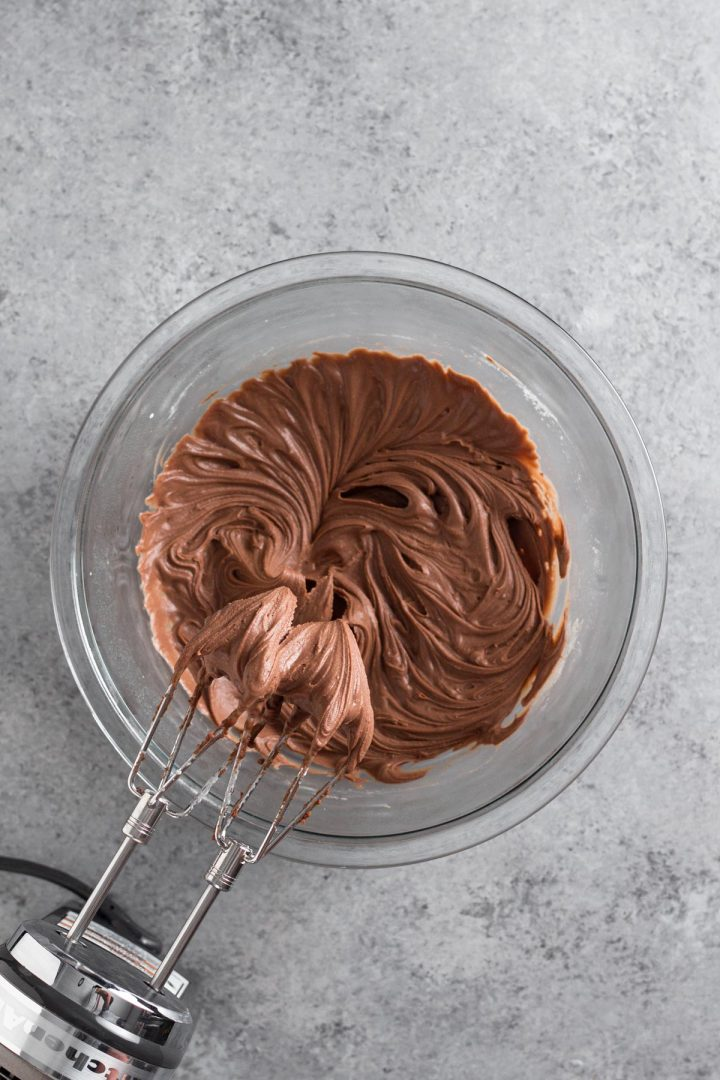 overhead view of chocolate peanut butter whipped cream blended in a glass bowl with a hand mixer