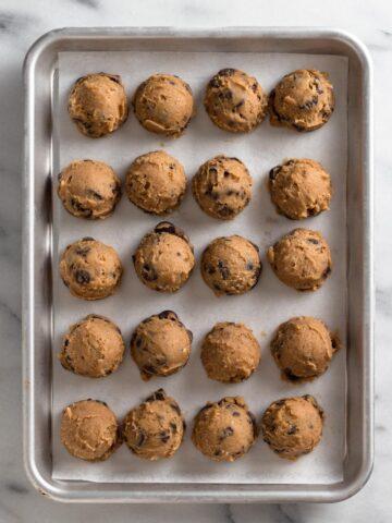 overhead view of cookie dough balls on a baking sheet