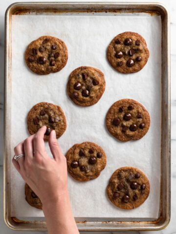 overhead view of chocolate chip cookies on a baking sheet with a hand adding chocolate chips on top of a cookie