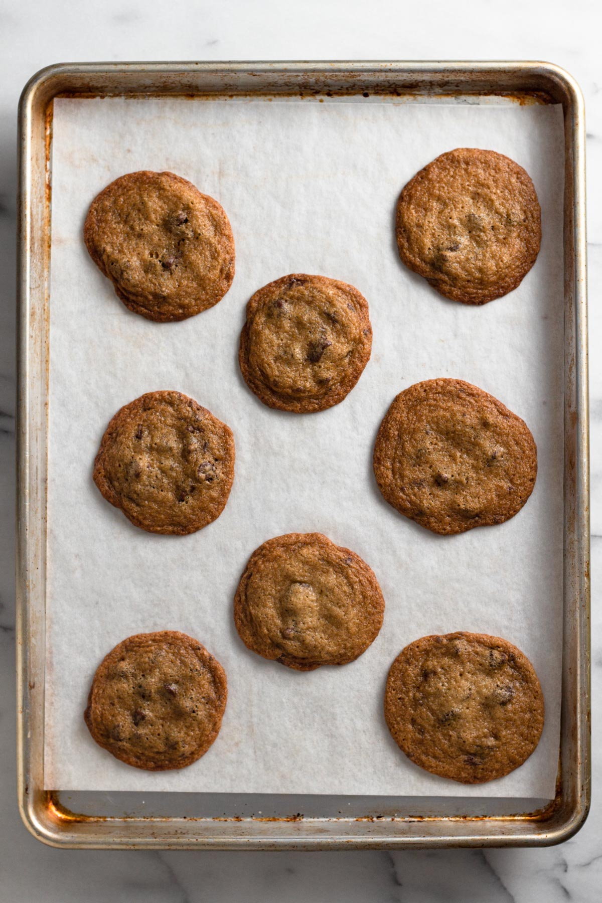 overhead view of baked chocolate chip cookies on a baking sheet