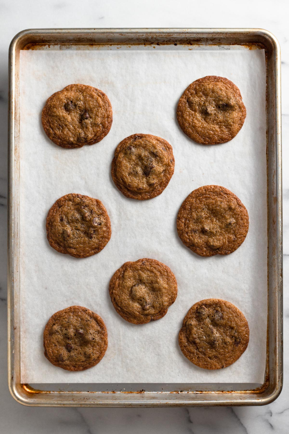 overhead view of perfectly round baked chocolate chip cookies on a baking sheet