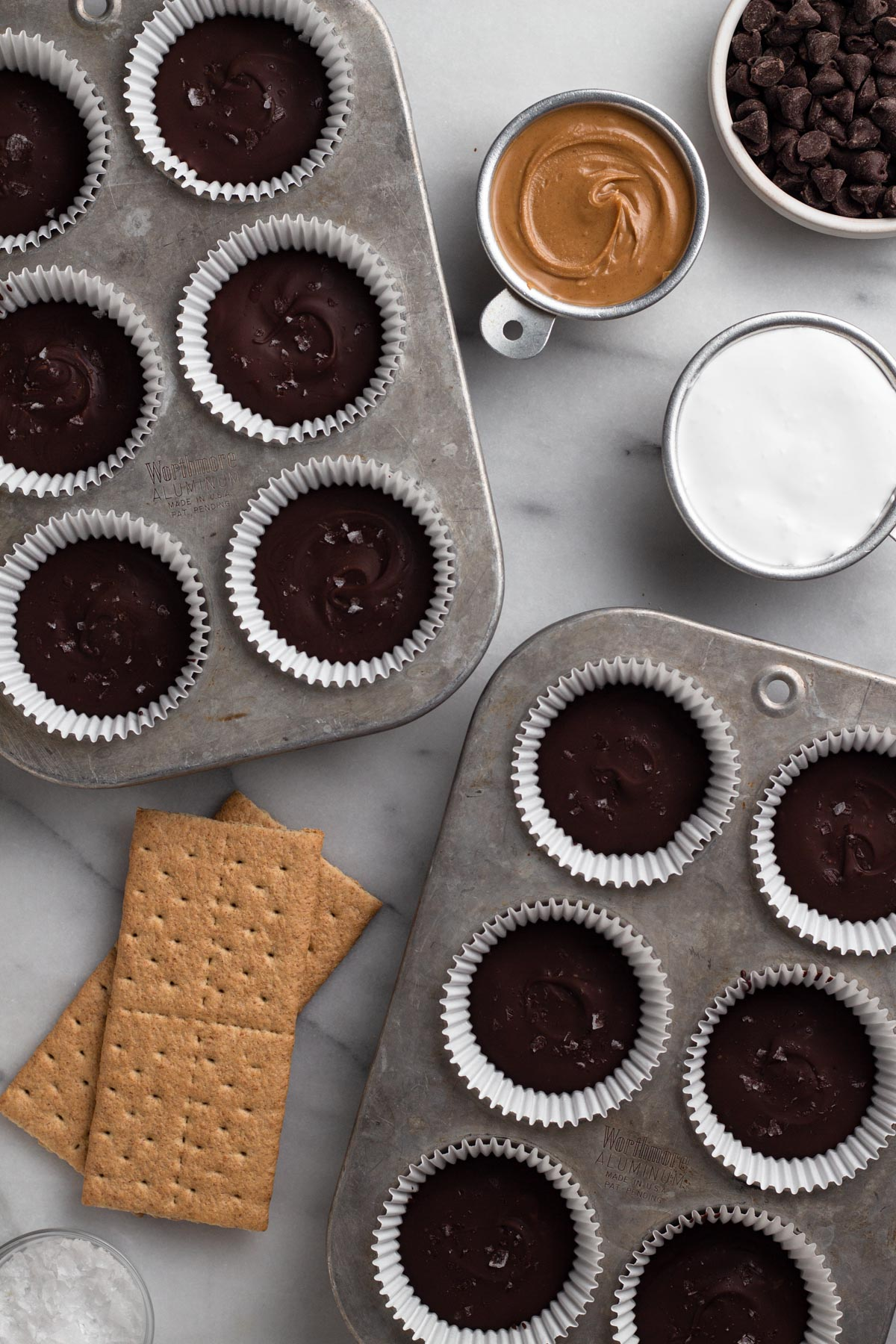 overhead view of peanut butter cups in muffin pan surrounded by recipe ingredients