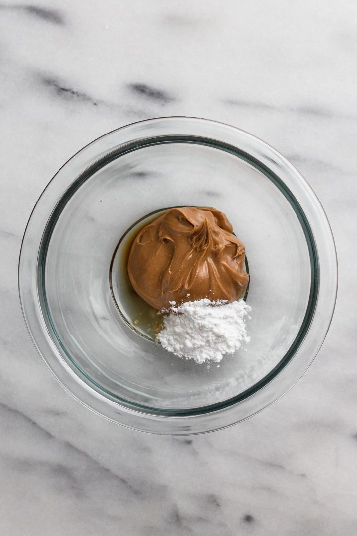 overhead view of peanut butter, confectioners' sugar, and vanilla extract in a glass bowl