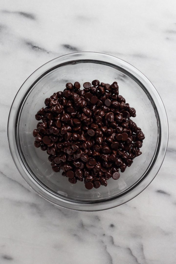overhead view of chocolate chips and oil in a glass bowl