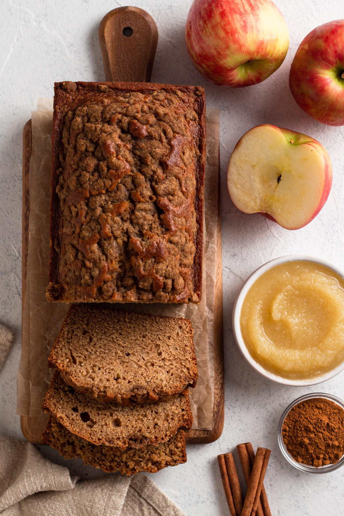 sliced loaf on a wooden cutting board next to apples, applesauce, and cinnamon