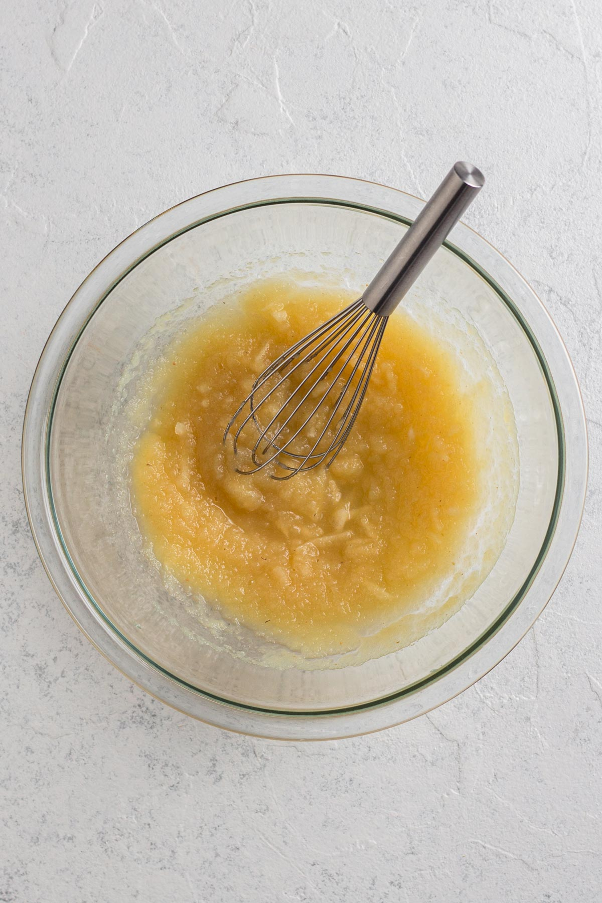 applesauce and grated apple in a glass bowl with a metal whisk