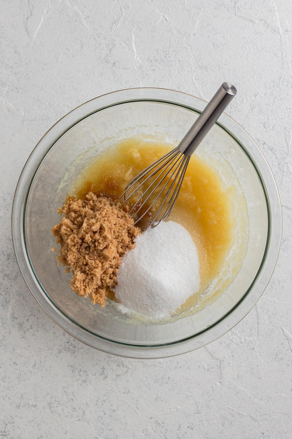 applesauce and sugars in a glass bowl with a whisk