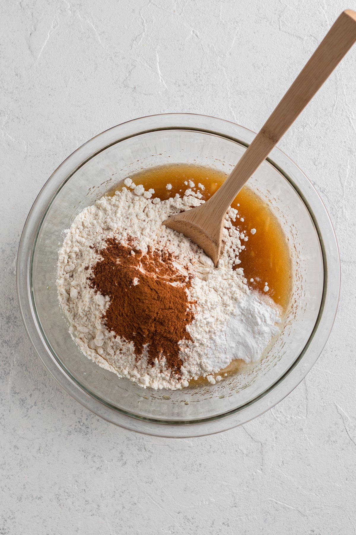dry ingredients added to wet ingredients in a glass bowl with a wooden spoon